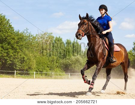 Female jockey galloping on horseback at racetrack during show jumping