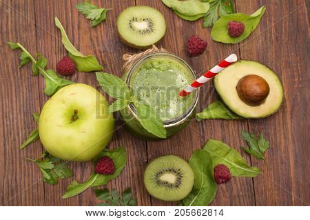healthy green smoothie with banana, spinach, avocado and kiwi in a glass bottles on a rustic background