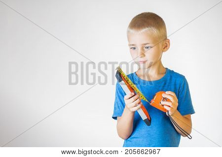 Boy is holding a roulette and construction level in his hands. Funny facial expression. Little handyman.