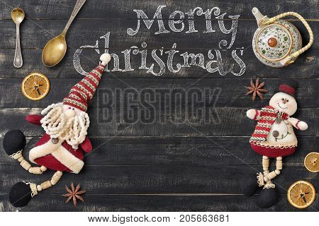 Merry Christmas Greeting Card with Santa Claus and Xmas Elements on Black Wooden Background. Retro Style. Place for Text.