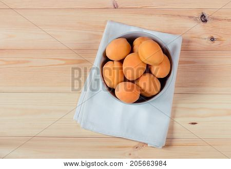 Bowl full of fresh apricots on wooden background. Top view.