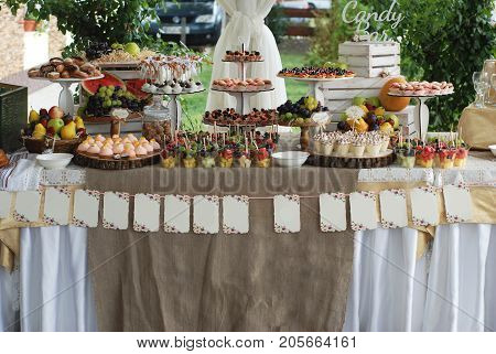 Macaroons, cakes, candies, sweets in a glass dish. Candy bar in wedding.