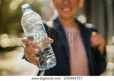 bottle of pure mineral water in the hand of a young happy girl. Autumn street day.