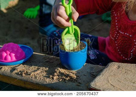 Little girl playing in a sandbox with a plastic shovel and a mug. In a mug filled with the sand lie next to a plastic plate and the mold. Summer day sun shining.