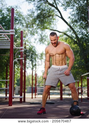 Full length of sporty and healthy muscular man exercising outdoors. Sexy young man with a muscular body on a natural background. Strong and perfect male body.