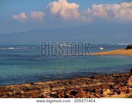 An isolated beach on the Hawaiian island of Lanai featuring a colorful beach umbrella.