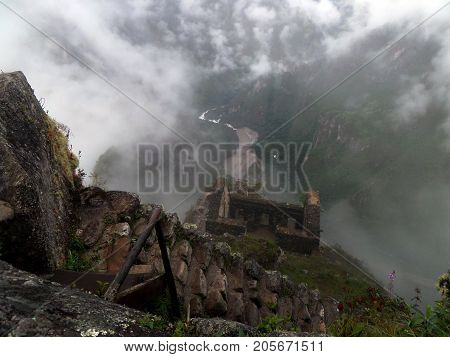 View from the towering heights of Wayna Picchu looking down from the peak through the mists to the Urubamba River flowing far below in the valley. In the foreground is