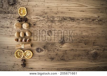 Nuts And Fruits Forming Shape Of Christmas Tree. Nuts Like Hazelnut, Walnut And Fruits Like Orange And Clove. Retro Brown Wooden Background With Copy Space