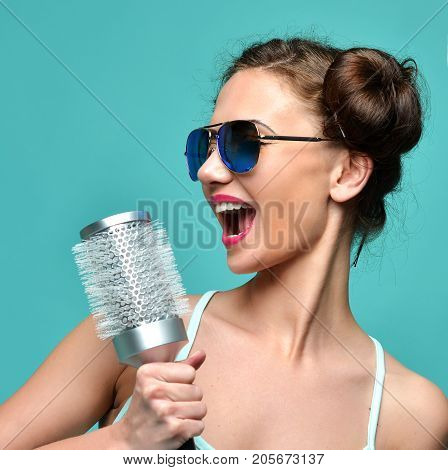 Closeup portrait of happy fashion brunette woman singing with big hair brush in modern aviator sunglasses on blue mint background