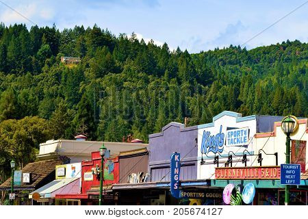 September 19, 2017 in Guerneville, CA:  Row of rustic retail stores and restaurants surrounded by hills with a lush green redwood forest taken in Guerneville, CA where tourists can enjoy these shops and restaurants while also enjoying outdoor recreation