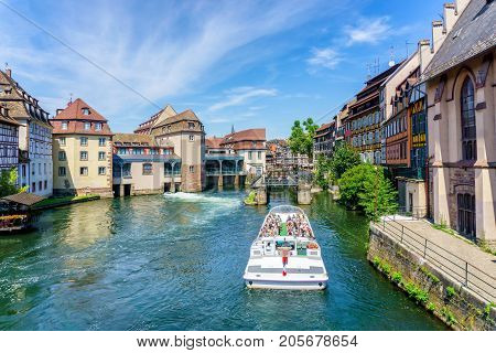 Traditional colorful houses in La Petite with tourists taking a boat ride along traditional colorful houses on idyllic river Lauch in summer Colmar Alsace France