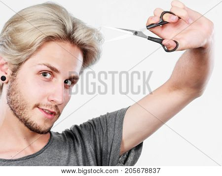 Hairstyle and haircut. Young cool guy barber holding shears tool ready to hair trimming. Blonde male with scissors creating new hairdo coiffure