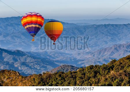Colorful hot-air balloons flying over the Doi Luang Chiang Dao with sunrise and morning mist at Chiang mai Thailand.