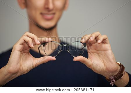 Eye vision problem theme. Glasses in man hands close-up