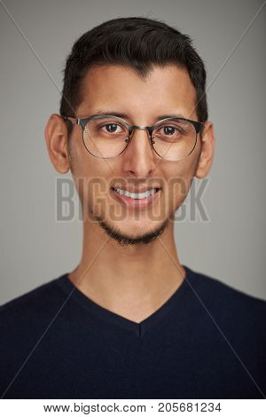 Portrait of young smiling latino man wearing glasses