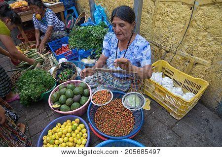 April 26 2016 San Pedro la Laguna Guatemala: mayan woman weighing produce with handheld scale