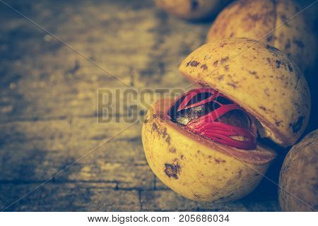 Nutmeg With Placenta-like Cover Of Seed Of Myristica Fragrant On Wooden Background.