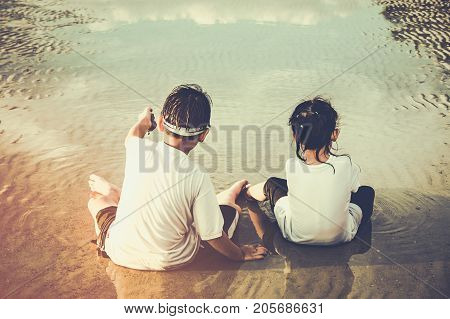 Asian Children Digging In The Sand. Concept Of Connecting Children With Nature.