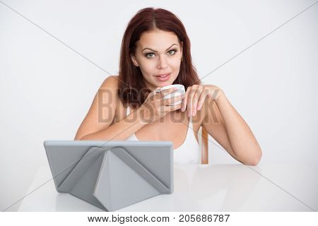 Portrait of young Caucasian woman sitting at touchpad, drinking coffee, looking at camera and smiling