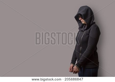 side view of a girl in a black hood with handcuffed hands isolated on a gray