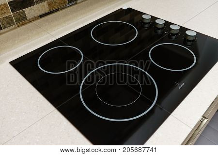 Modern black induction stove cooker hob or built in cooktop with ceramic top in white kitchen interior
