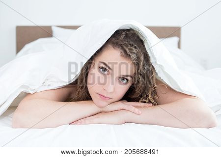 Closeup portrait of smiling middle-aged beautiful woman looking at camera and lying under blanket in bed in bedroom. Front view.