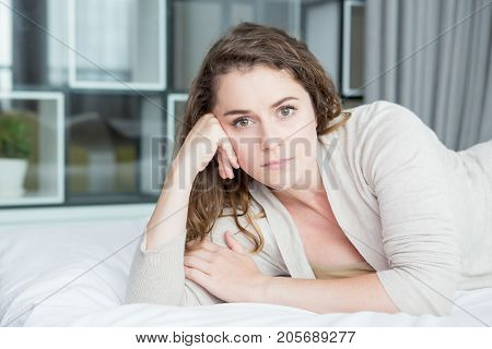 Closeup portrait of content middle-aged beautiful woman looking at camera, leaning head on hand and lying on bed in bedroom. Front view.