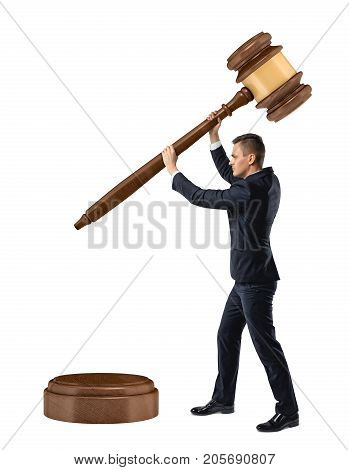 A small businessman on isolated white background holds and lowers a giant judge gavel on a sound block. Self judgement. Legal prosecution. Business and competition.