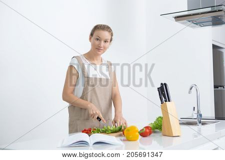 Calm young woman making favorite recipe at modern kitchen. Confident beautiful housewife cutting vegetables on board and looking at camera. Recipe book concept
