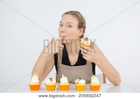 Funny woman licking finger with buttercream and looking at camera. Attractive confectioner tasting icing for cupcakes. Mouthwatering concept