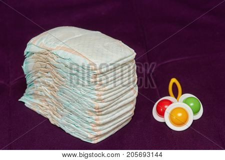 Stack of diapers or nappies with colorful rattle on purple background closeup