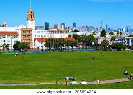 September 19, 2017 in San Francisco, CA:  People relaxing on a manicured lawn overlooking Downtown San Francisco taken at Dolores Park where people can relax and enjoy recreational activities while watching spectacular views of the city taken in San Franc
