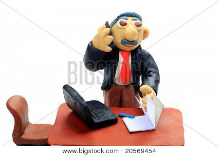 Shot of a plasticine businessman working at the office. Isolated over white background.