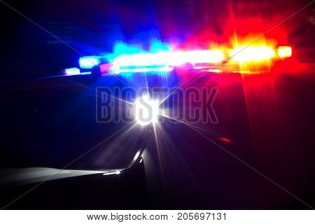 Red and Blue Emergency Lights Flashing on Police Car at Night