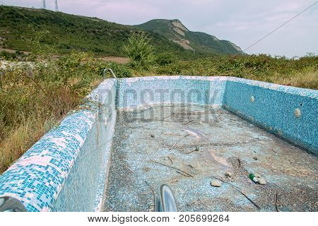 Abandoned swimming pool with mountain background at a country