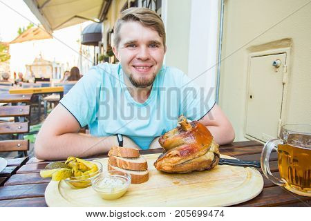 man eating knuckle of pork and drinks beer.
