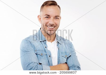 Cheerful man. The portrait of a handsome young man in a denim shirt on top of a white t-shirt standing isolated on white background while folding arms and smiling