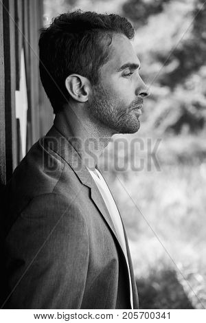 Handsome guy with stubble in profile black and white
