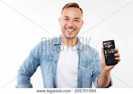 Favorite app. Upbeat young man listening to the music in headphones and showing his favorite application for streaming music