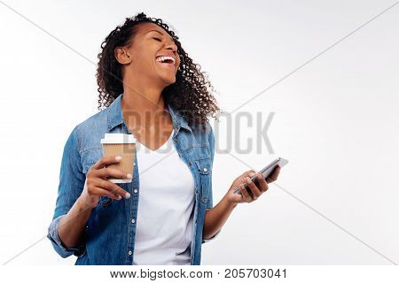 Hilarious message. Charming upbeat woman laughing at a funny text message received on her phone while holding a cup of coffee
