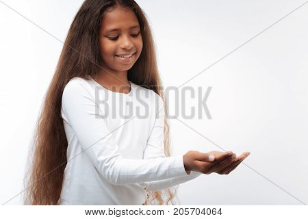 Delicate girl. Beautiful pre-teen girl with a swarthy complexion and a long auburn hair cupping her hands as if carrying something small and precious in them