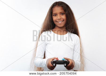 My hobby. Adorable pre-teen girl with a swarthy complexion and a long auburn hair posing on a white background with a video game controller in hands