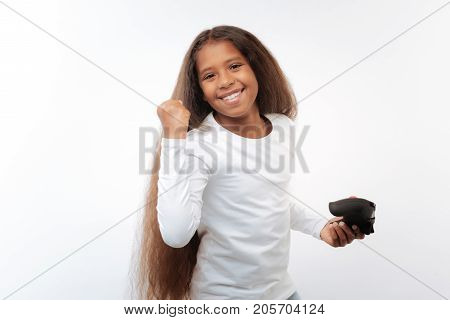 Mood-boosting win. Happy pre-teen girl raising her hand in a celebrating gesture while holding a video game controller, having won a game