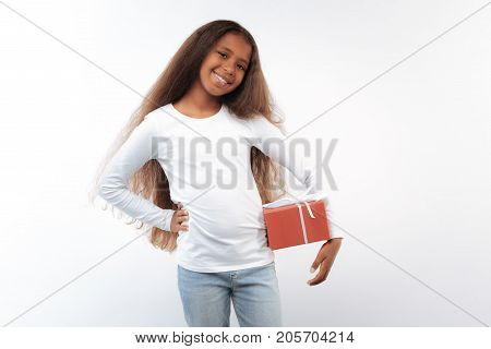 Best gift. Charming pre-teen girl with a long auburn hair and swarthy complexion posing on a white background, holding one hand on waist and pressing gift box with the other one