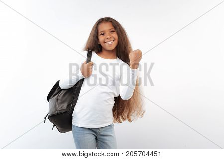 Reaching success. Pleasant cheerful girl with a long auburn hair posing on a white background and raising her hand in a gesture of celebration after accomplishing her goal