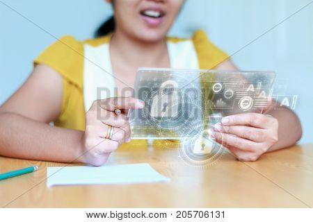 Close up shot Asian woman using clear tablet for futuristic cyber technology concept with HUD GUI User interface element hallow depth of field