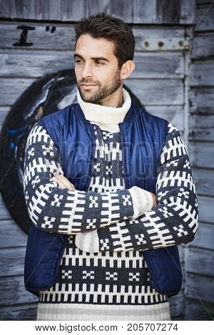 Handsome rugged guy in patterned knitwear and body warmer looking away