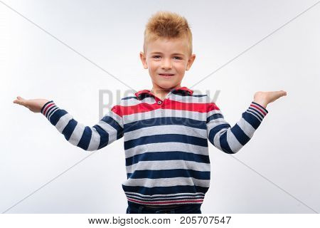 Full of life. Cheerful adorable boy in a striped long sleeve t-shirt posing on a white background and spreading his hands wide, being full of energy and life