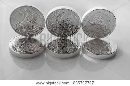 On a gray background are silver coins of an investment silver from a British mints. Dragon of Wales Lion of England and Griffin of Edward III.