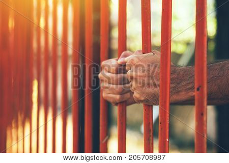 Male hands behind prison yard bars incarcerated captivated person in jail